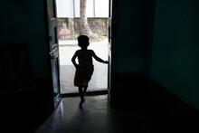 A Little Girl Exiting Through A Door