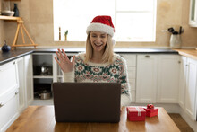 Woman Wearing Santa Hat Having A Video Chat On Her Laptop At Home