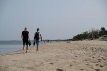 Two Men Walking Along The Beac...