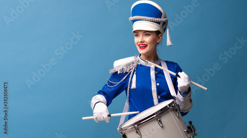 Photo drummer in a blue uniform drums on a drum, show program and celebration