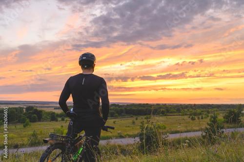 Back view of anonymous man in helmet admiring cloudy sundown sky during bicycle Wallpaper Mural