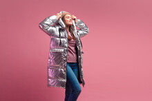 Fashionable And Modern Young Woman In A Puffy Light Down Jacket Throws A Hood Over Her Head.