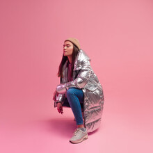 Stylish Fashionable And Modern Young Woman In A Puffy Light Down Jacket. The Jacket Is A Silver Metallic Color.