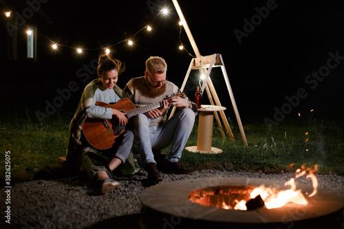 Fototapeta Man teaching girl play a guitar on autumn night picnic