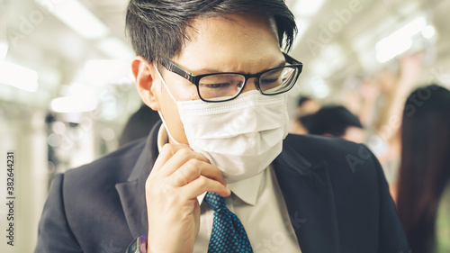 Young man wearing face mask travels on crowded subway train Canvas Print