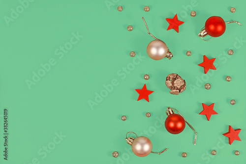 Fototapeta Christmas flat lay with seasonal golden and red tree ornament baubles, wooden red stars and golden snowballs on green background with empty copy space obraz