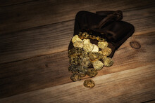 Leather Pouch With Poured Gold Coins On Wooden Background. Money, Financial, Growth Concept.