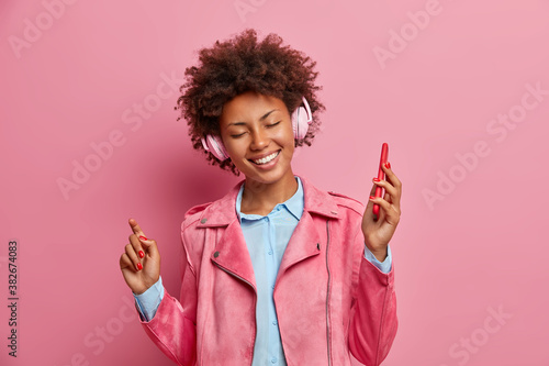 Cheerful dark skinned female model dances happily and holds mobile phone in hand uses stereo headphones enjoys pleasant sound listens favorite songs from playlist poses against rosy background