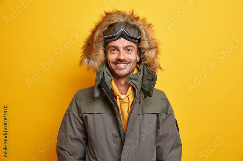 Happy European man in jacket with fur hood feels warm and comfortable during win Fototapet
