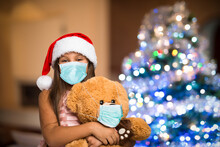 Girl And Teddy Bear Wearing A Mask, Christmas Coronavirus And Pandemic Concept
