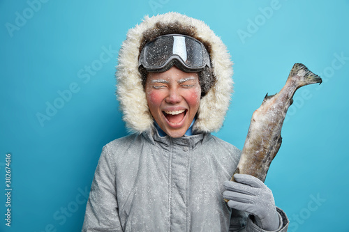 Fotografía Happy emotional woman with red face exclaims gladfully as caught fish enjoys winter holidays has active rest dressed in outerwear poses against blue wall during heavy blizzard
