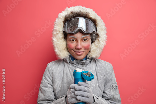 Active female snowboarder dressed in warm outerwear has red skin and frozen face during cold winter weather drinks hot beverage from thermos isolated on vivid pink background. Recreation concept