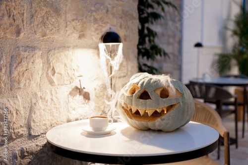 Halloween pumpkin. Table with coffee and jack o lantern pumpkin. Holiday interior and decoration in cafe indoors.