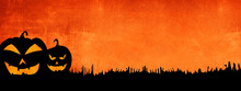 HALLOWEEN Background Banner Wide Panoramic Panorama Template -Silhouette Of Scary Carved Luminous Cartoon Pumpkins Isolated On Dark Orange Night Texture