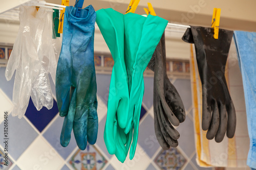 Obraz na plátně Several pairs of rubber gloves hang on  dryer