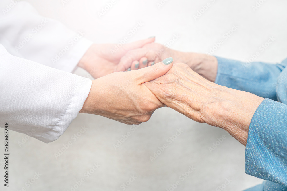 Fototapeta Helping and care for the elderly concept.Young nurse hands holding an old hands of senior woman.