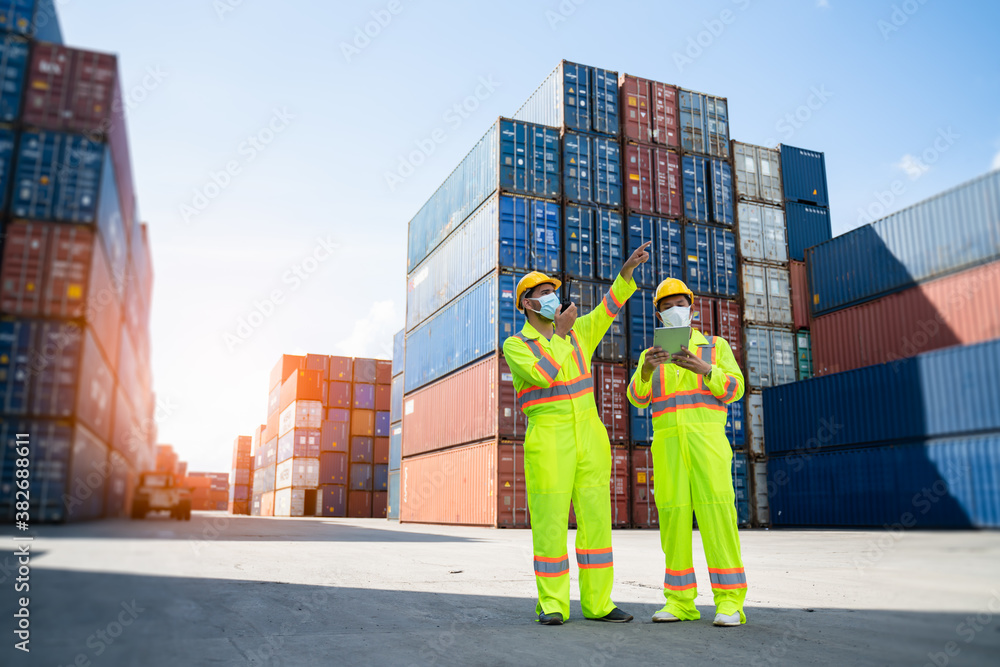 Fototapeta Engineer or worker man using a smartphone wearing mask and safety yellow helmet to protection for coronavirus in during concern about covid pandemic.Workers wearing protective mask working in cargo.