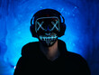 Portrait of a guy with headphones and a glowing Halloween mask . Autumn party