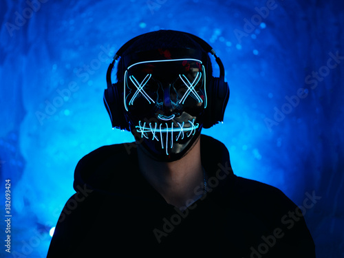 Fotomural Portrait of a guy with headphones and a glowing Halloween mask