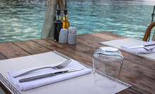 Close Up Of A Table In A Fine Floating Restaurant On The River With A Glass, Knife And Fork, Oil And Vinegar