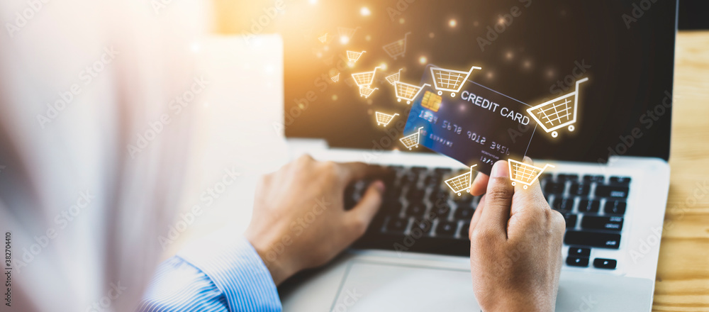 Fototapeta Woman using Credit card filling in billing information in computer laptop purchasing products on ecommerce store online payment shopping, selective focus, accessible internet money transaction