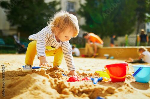 Fototapeta Adorable little girl on playground in sandpit