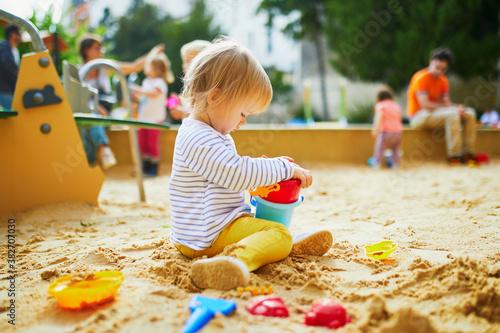 Obraz na plátně Adorable little girl on playground in sandpit