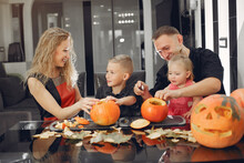 Family In A Kitchen. People Prepares To Halloween. Family Cuts Pumpkins.