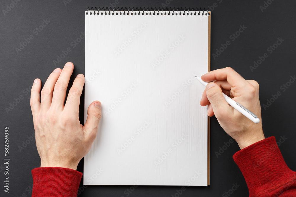 Fototapeta notebook with black pen in hands