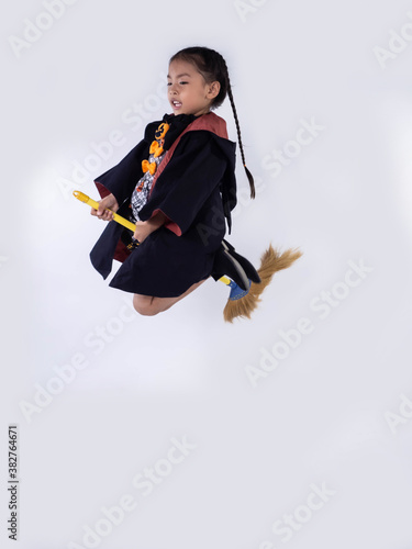 Fotografie, Obraz Asian children girl in witch dress costume Riding a broom for Halloween decorati