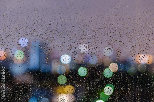 Fototapeta Rain drop on window with colorful bokeh lights.