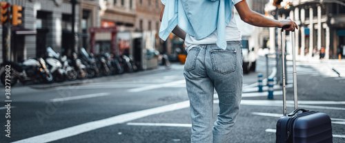 Fotografie, Obraz Young traveling woman with suitcase on a sunny city street
