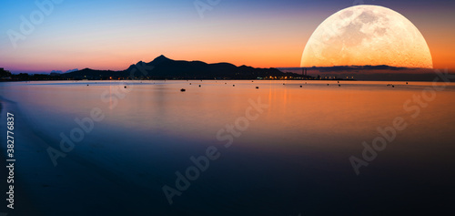 Fantastic landscape with a giant moon against the backdrop of a seascape