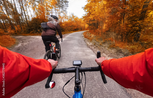Cyclists on bicycles ride along the road in the autumn forest Canvas