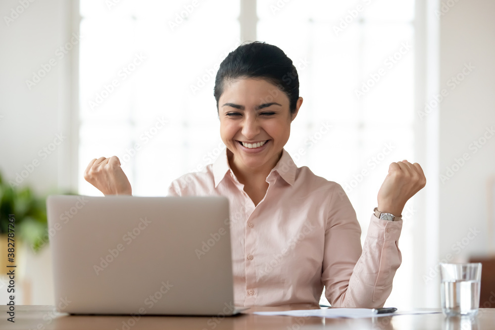 Fototapeta Overjoyed young indian female employee sit at desk in office look at laptop screen read good news online. Happy millennial ethnic woman worker feel excited euphoric with message or notice on computer.