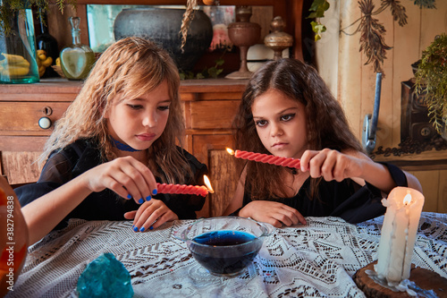 Foto Two cute girls aged 9 years in witch costumes in an old house on Halloween dripping candle wax in blue water and conjuring