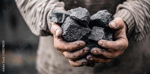 Photo Miner holds coal palm. Concept mining, Top view
