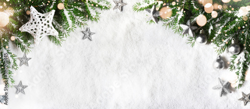 Fotografie, Obraz Christmas background, green pine branches, cones on snow background and light
