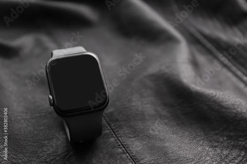 Fototapeta Stylish smart watch on black leather fabric, closeup. Space for text obraz
