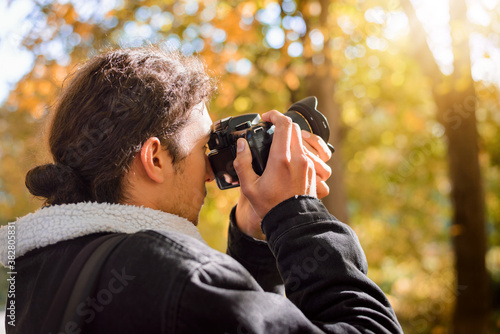 Young professional male photographer takes pictures in the autumn park Fotobehang