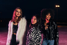 Fashionable Girls Standing Together On Roof At Night Under Neon Lights. Multi-ethnic Group Of Women Posing Outdoors And Looking At Camera.