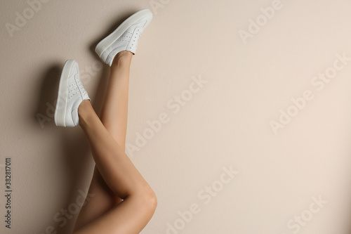 Fototapeta Woman wearing shoes on beige background, closeup. Space for text obraz