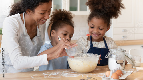 Photo Head shot smiling beautiful african ethnicity mother adding flour, making dough with happy small biracial son and daughter, involved in preparing homemade pastry biscuit or pizza together in kitchen