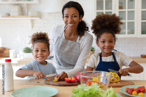 Fotografering Portrait of happy young african american mother enjoying cooking healthy vegetarian food together with joyful little cute children in modern kitchen, smiling adorable family looking at camera