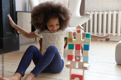 Photo Overjoyed young funny adorable child girl finishing constructing high toy building with wooden blocks, celebrating balance success alone in living room, emotional female kid entertaining at home