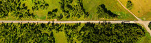 Aerial View On Railway Under Construction, Among Forests, Fields And Villages. Road Works In The Forest And In Fields. Dirt Road In An Open Area. Railroad Construction Through Fields And Meadows