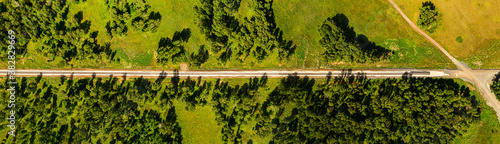 Fototapeta Aerial view on railway under construction, among forests, fields and villages. Road works in the forest and in fields. Dirt road in an open area. Railroad construction through fields and meadows obraz