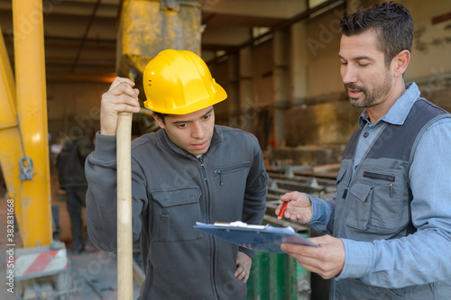 Fotografia, Obraz engineers discussing over clipboard at construction site