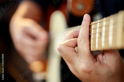 close up hand young man playing electric guitar at recording studio rehearsal base. rock music band.