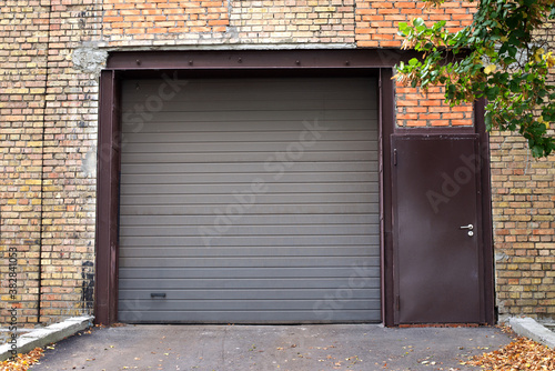 Automatic Electric Roll-up Gate Or Push-up Door. Shutter door or roller door and brick wall exterior. Brown Automatic shutters in a house. gates in the garage